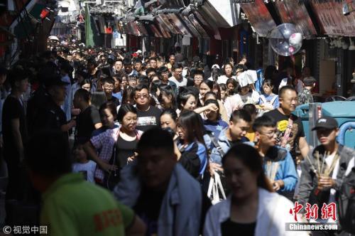 资料图:去年中秋,在山东济南芙蓉街老街巷景区,来自全国的游客聚集在老街里,形成人海景观。 图片来源:视觉中国