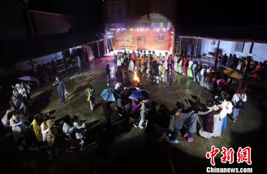 摩梭小伙和摩梭姑娘与游客们手拉着手跳舞。 王磊 摄